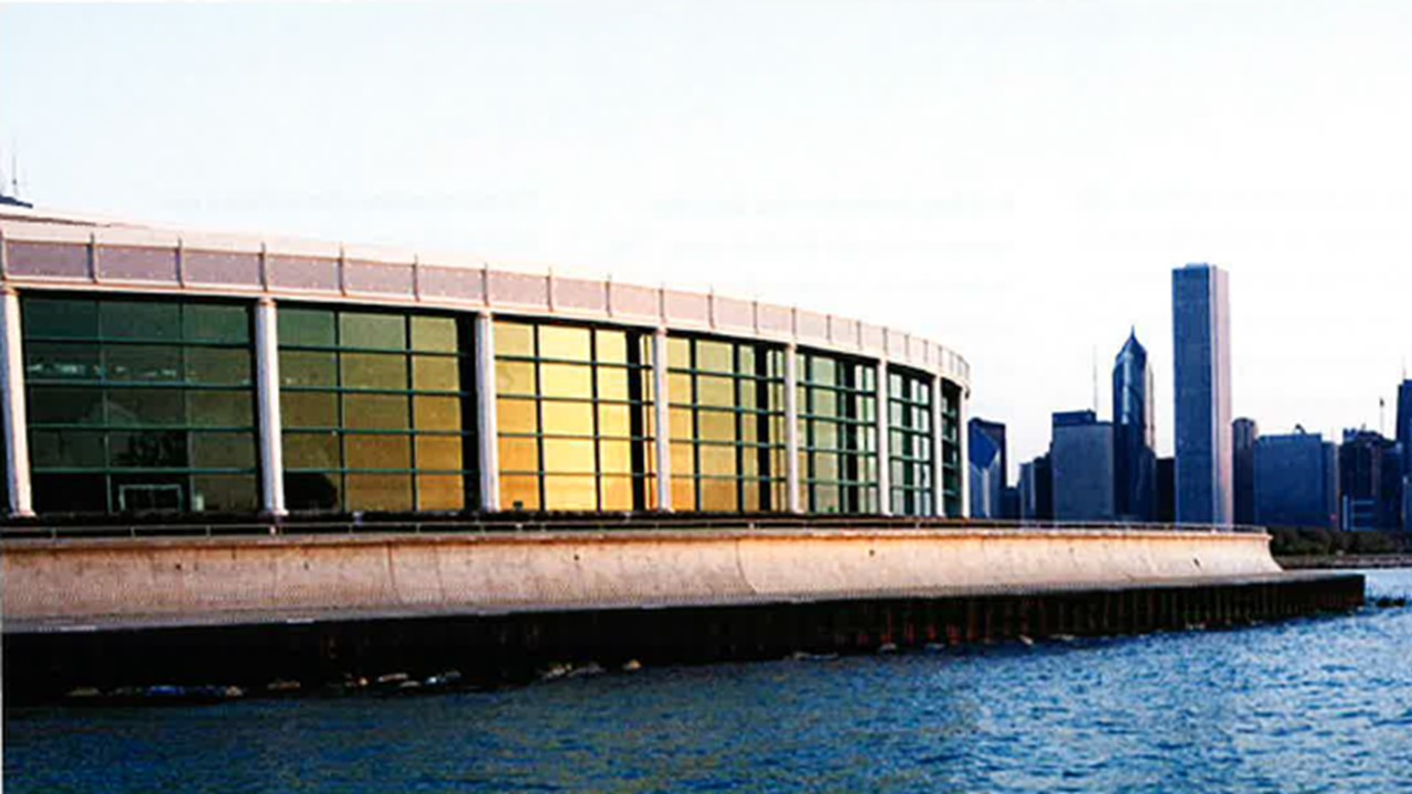 View of the Shedd Aquarium from the river with a curved concrete and glass wall with the city of Chicago in the background.