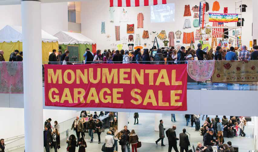 The Monumental Garage Sale at the Museum of Modern Art with a line of people mulling around and several carpets displayed over a glass railing.