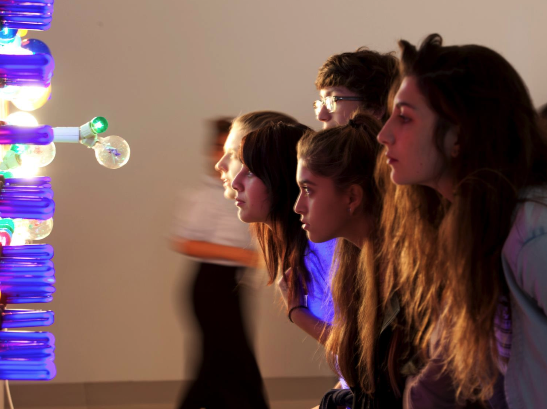 Four young students staring at a sculpture of neon and incandescent lightbulbs - their faces illuminated by the bulbs