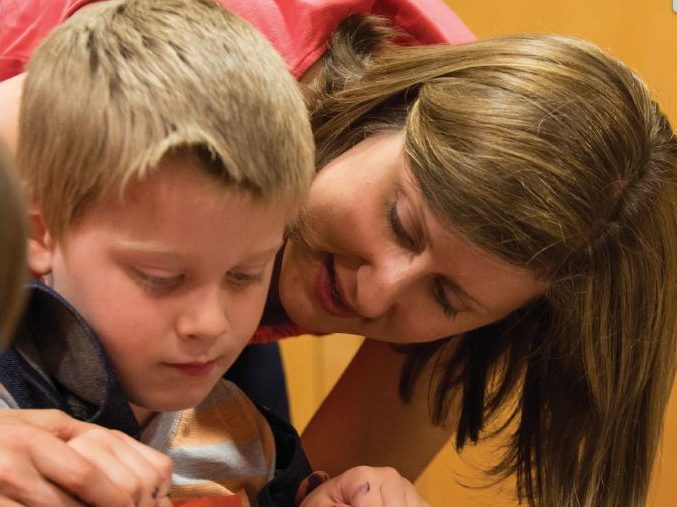 A mother and son work on an art project with paint.