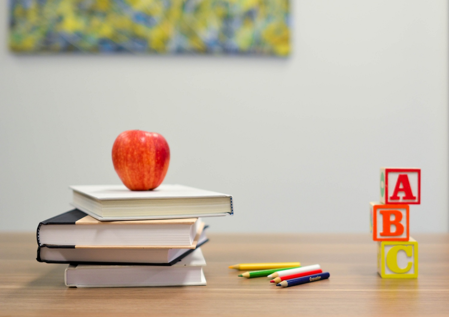 An image of a red apple stacked on top of several books on a wooden desk.