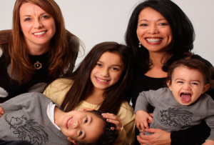 A family with two women and three children, smiling.