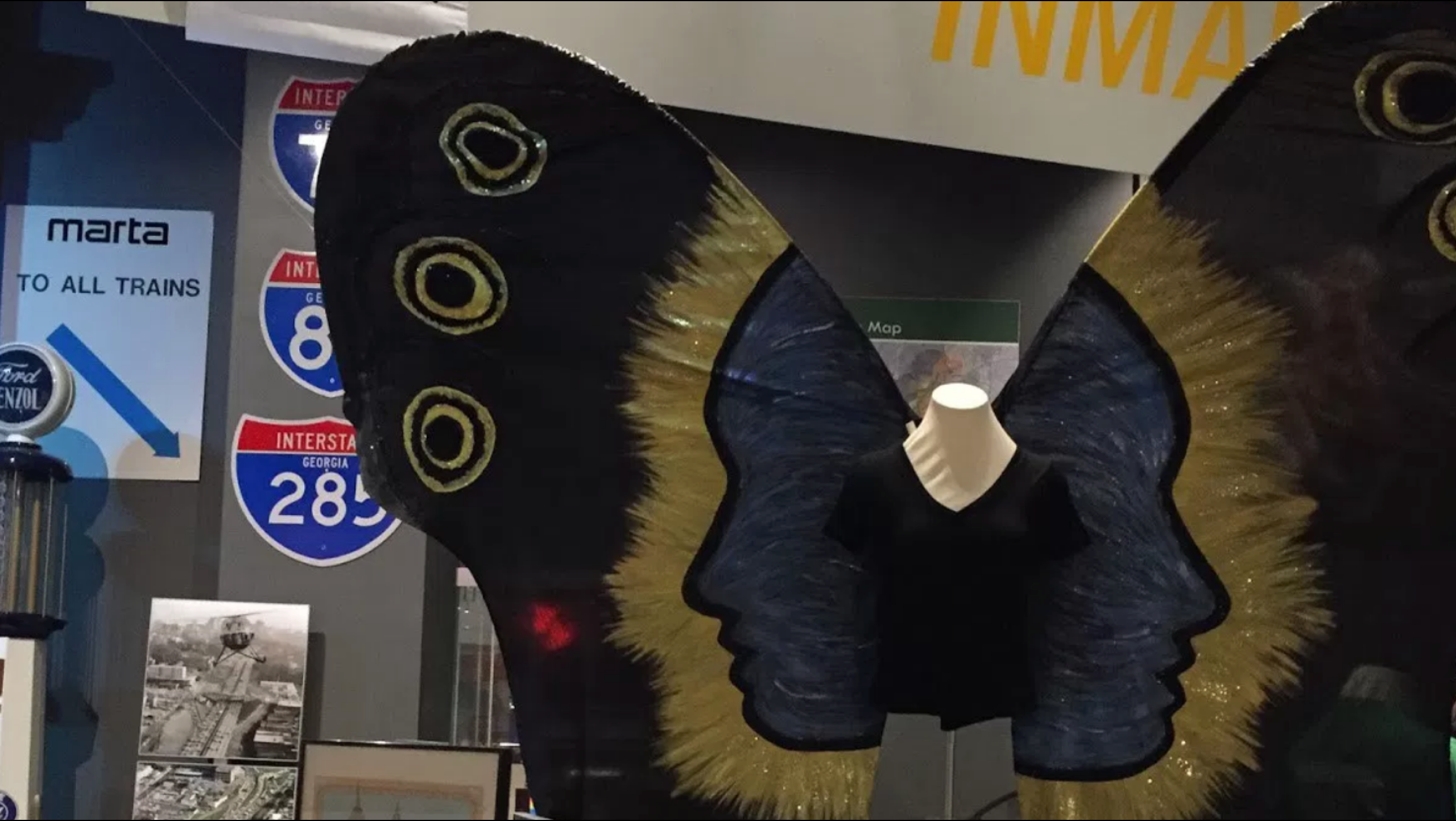 A piece of art takes up the entire composition. A mannequin bust (the type with just the torso) is dressed in a black v-neck tshirt with oversized dark butterfly wings. The wings depict two human faces in profile looking out from the body in blue. Each has a yellow aura around it which fades out to black. There are three yellow circles on the top wing tips. This piece of art is in an exhibition with a lot of other art just barely visible.