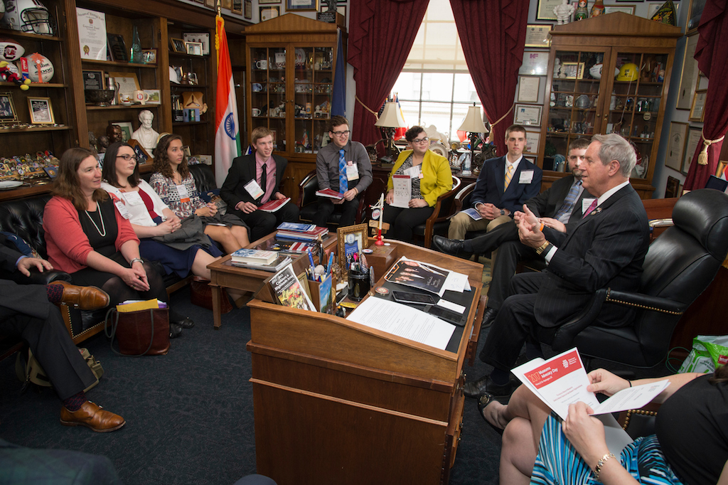 Nine people gather around a wooden desk wearing suits and listening to a representative talk.