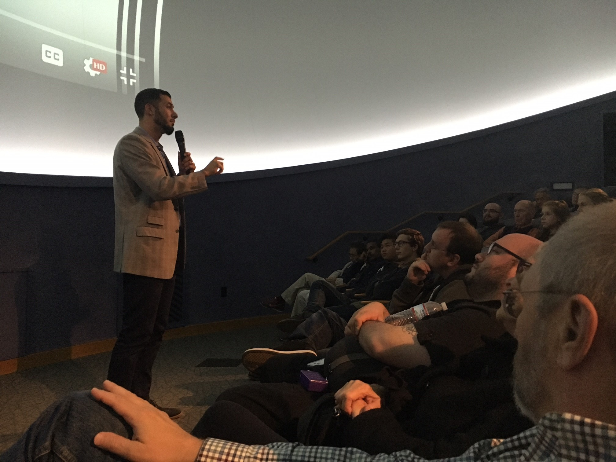 Image of a man standing before a group of interested attendees watching a screen.