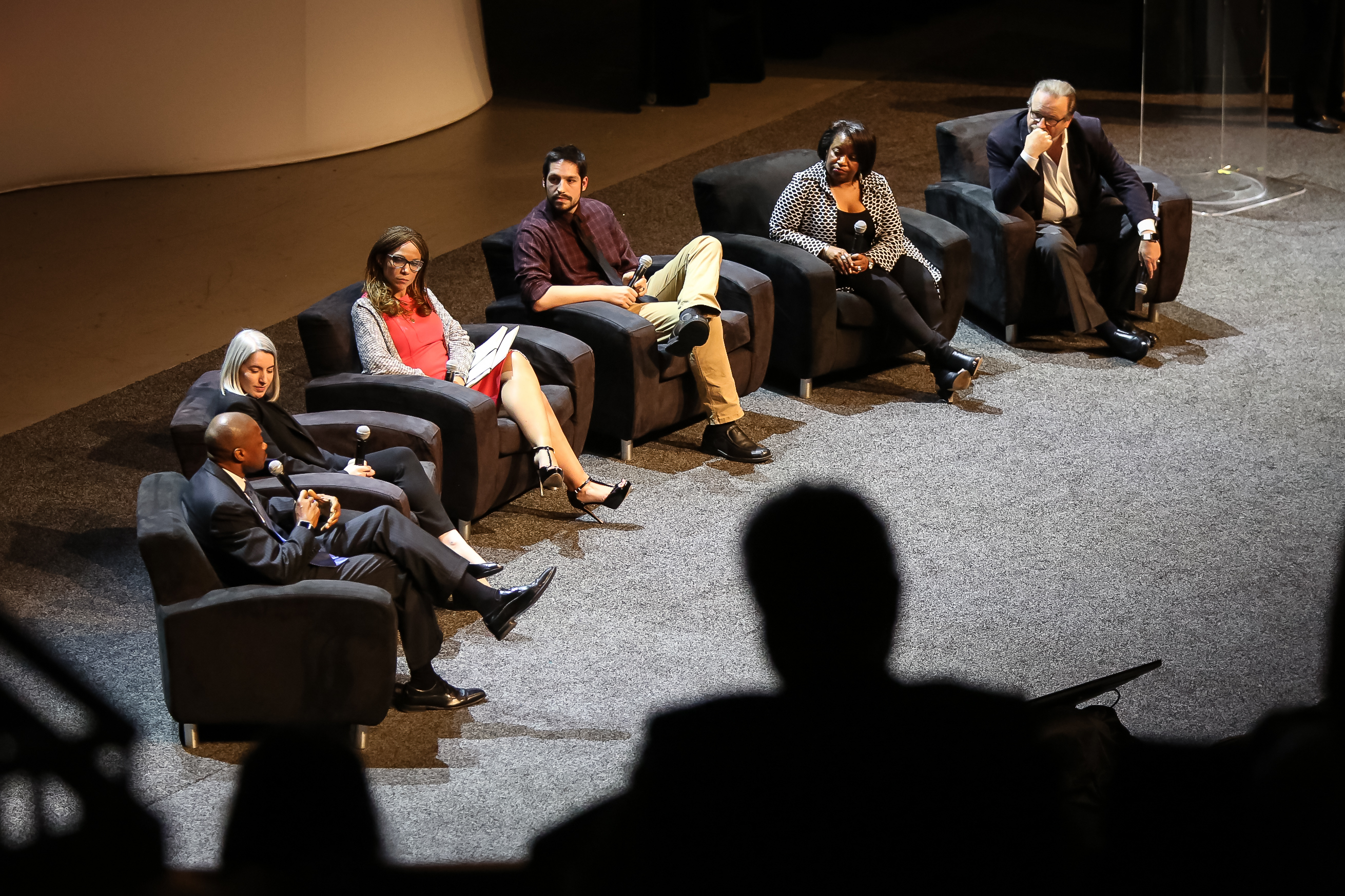 Six people sitting in chairs on a stage