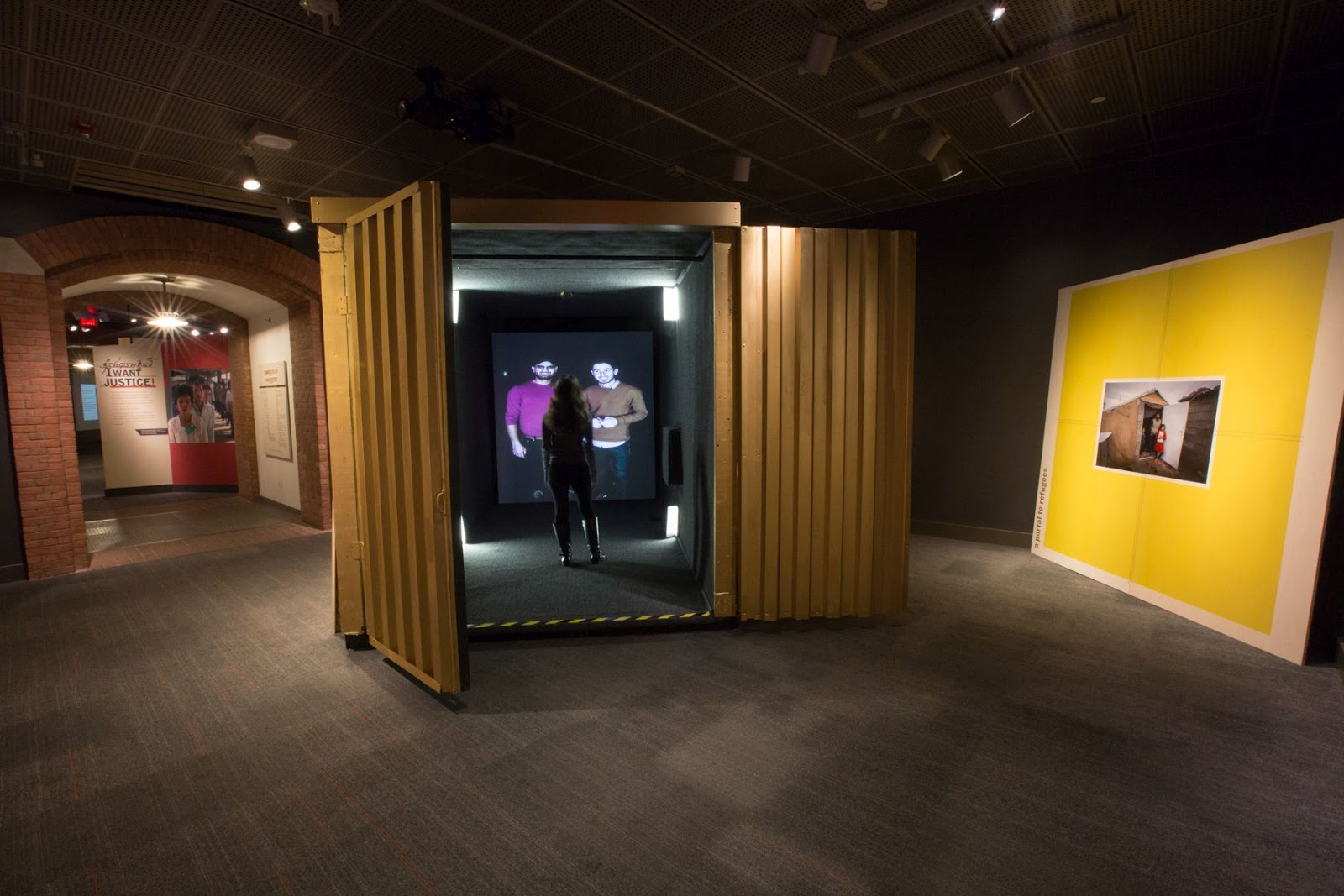 Image of a shipping container with a video portal at the far end of it and a person inside talking to two other people from the portal