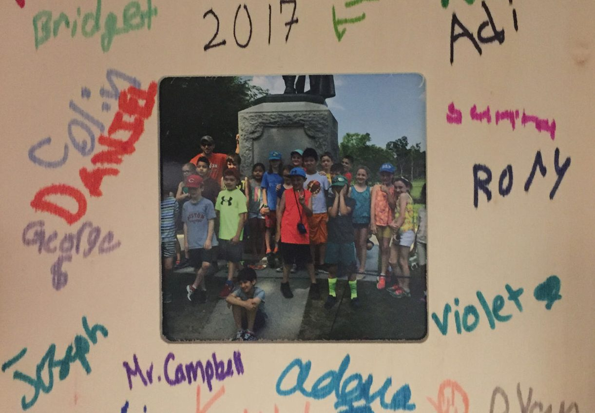 Group of children surrounding a statue framed with mat signed by all of the kids