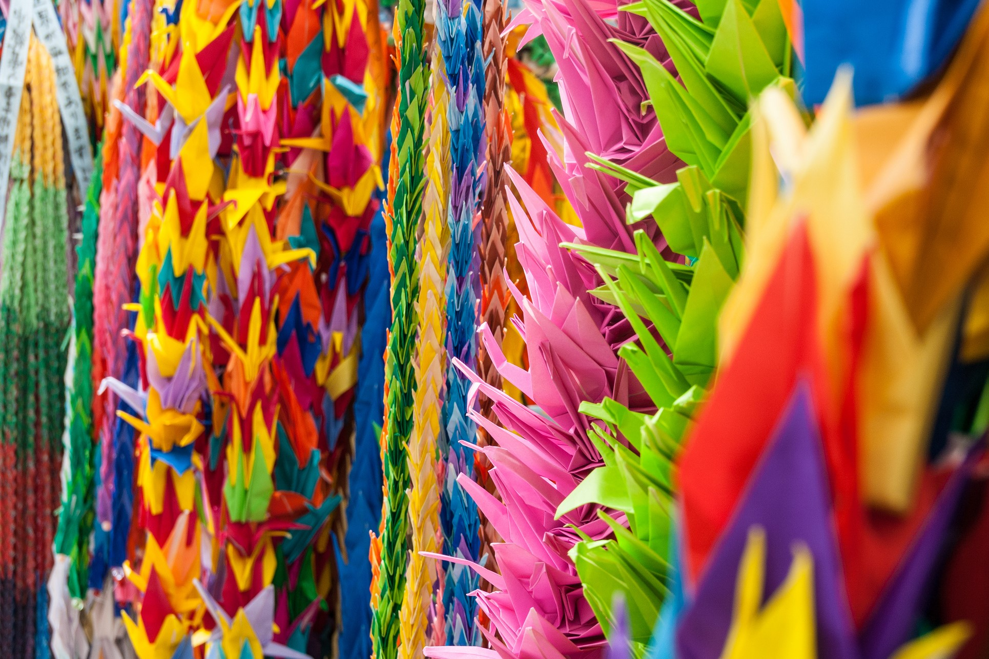 A closeup of brightly color peace crane hanging from garland