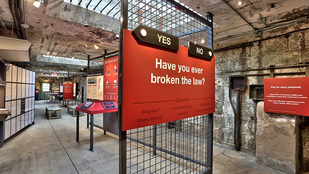 "Image of the exhbition with a closeup of one of the labels saying ""Have you ever broken the law?"""