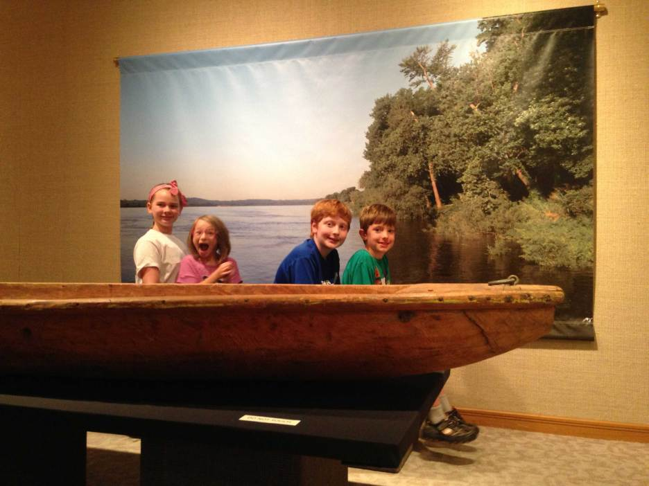 A group of four kids smile at the camera sitting in a boat in an interactive display