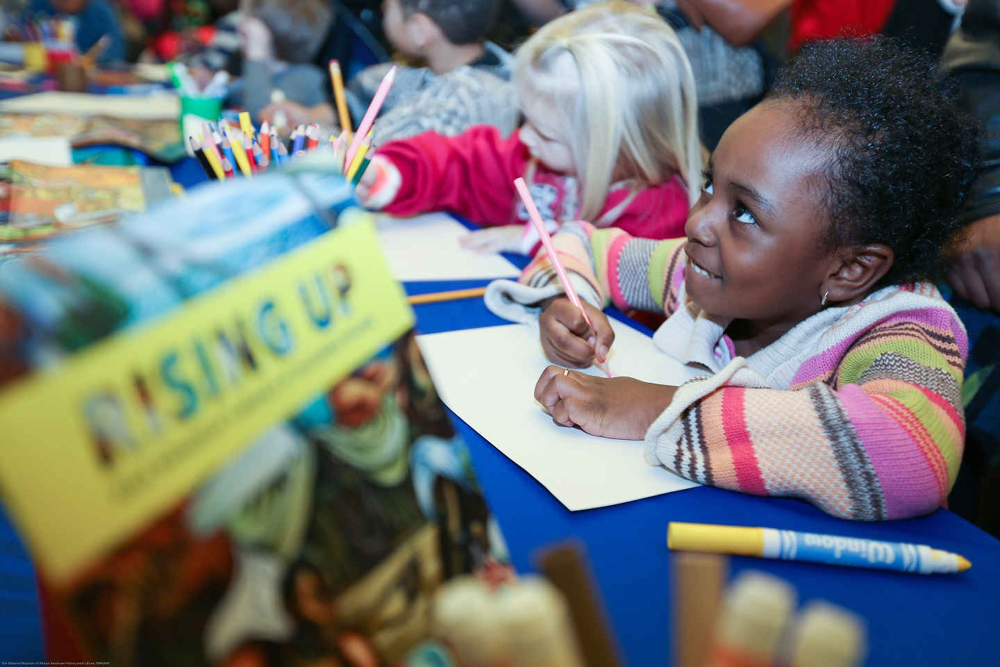 A group of young children sit at a long table coloring and writing. One youngster is smiling up at someone off-camera.