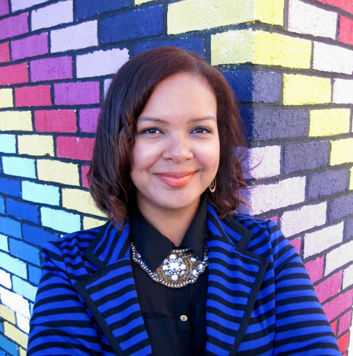 Woman smiling in front of a colorful brick wall wearing a striped blue jacket and black shirt
