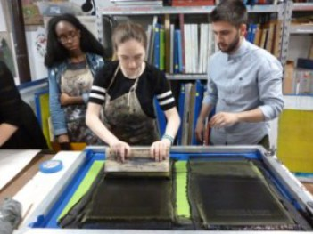 Three students work at a print station.