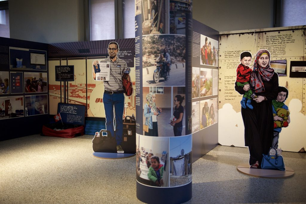 Image of an exhibit with two figures shown standing with children
