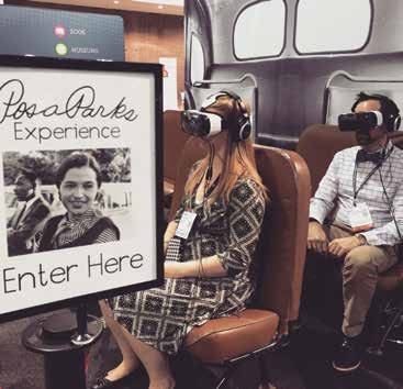 "Two visitors sit on bus seats wearing virtual reality glasses with a sign in the foreground saying ""Rosa Parks Experience Enter Here"""