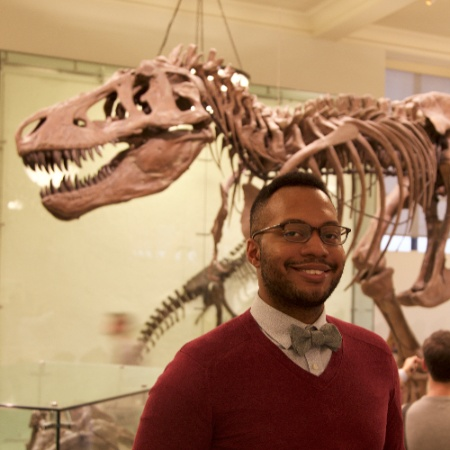 A man stands in front of a T-Rex skeleton wearing a red sweater, white shirt, with a blue or grey bowtie