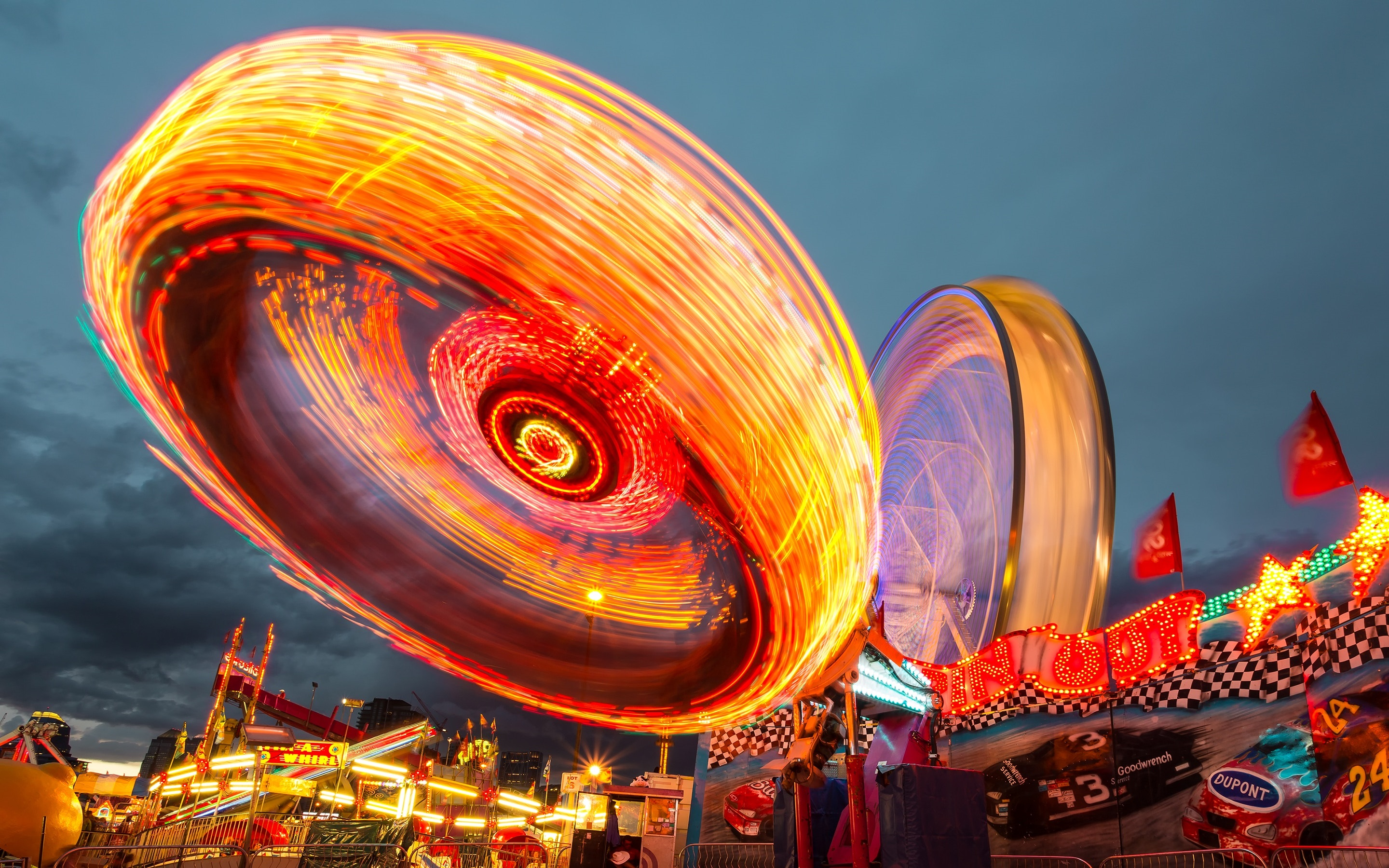 Image of an amusement park ride taken at night. Lights are blurring together to show motion and rides are lit brightly red, orange, and burgundy.