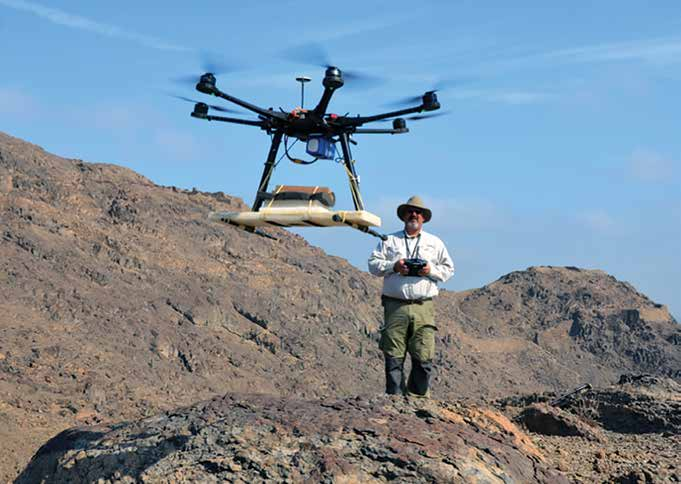 A man stands on a rocky hillside controlling a large drone in the foreground
