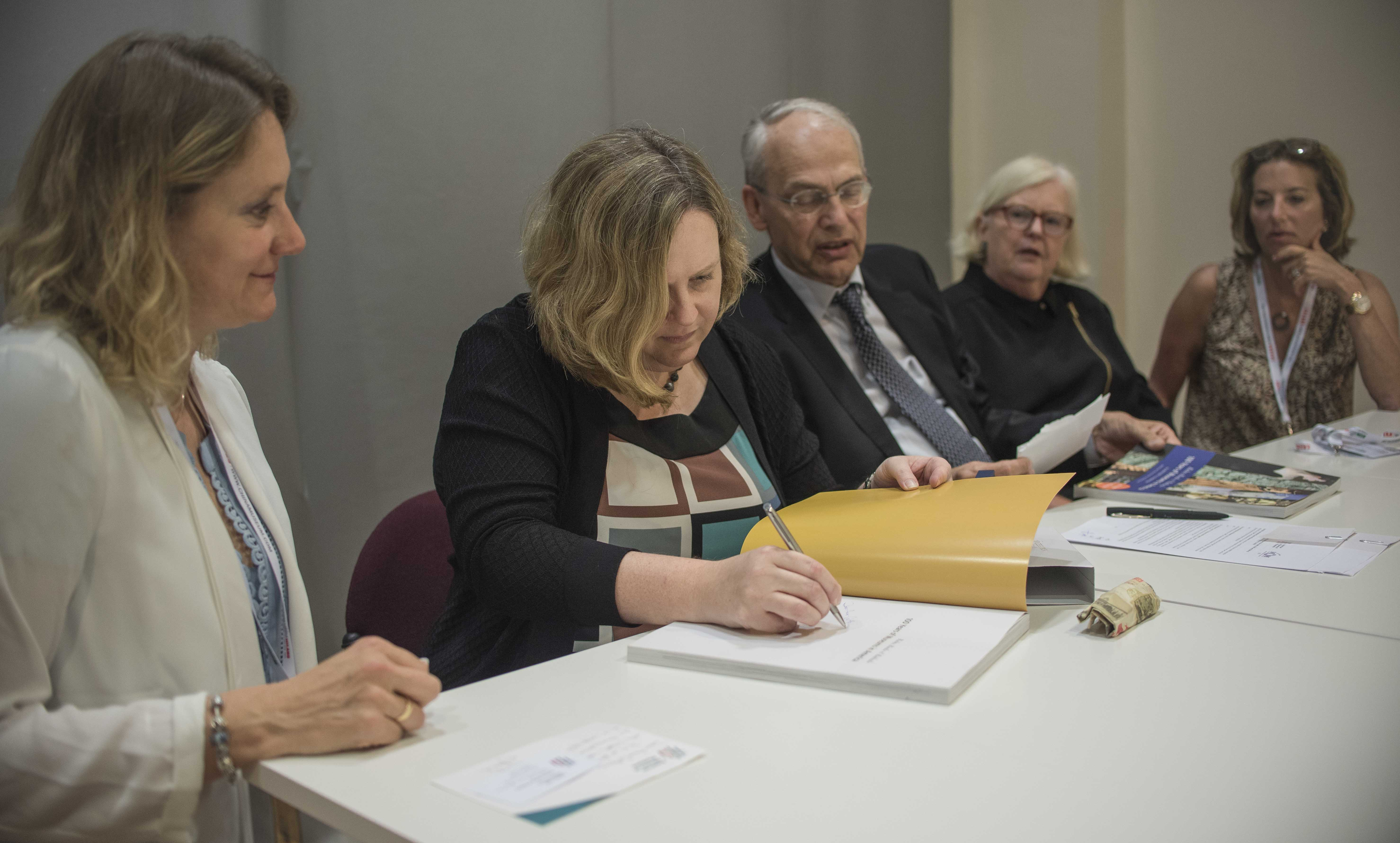 A group of people sit at a long table. Laura Lott is signing the document.
