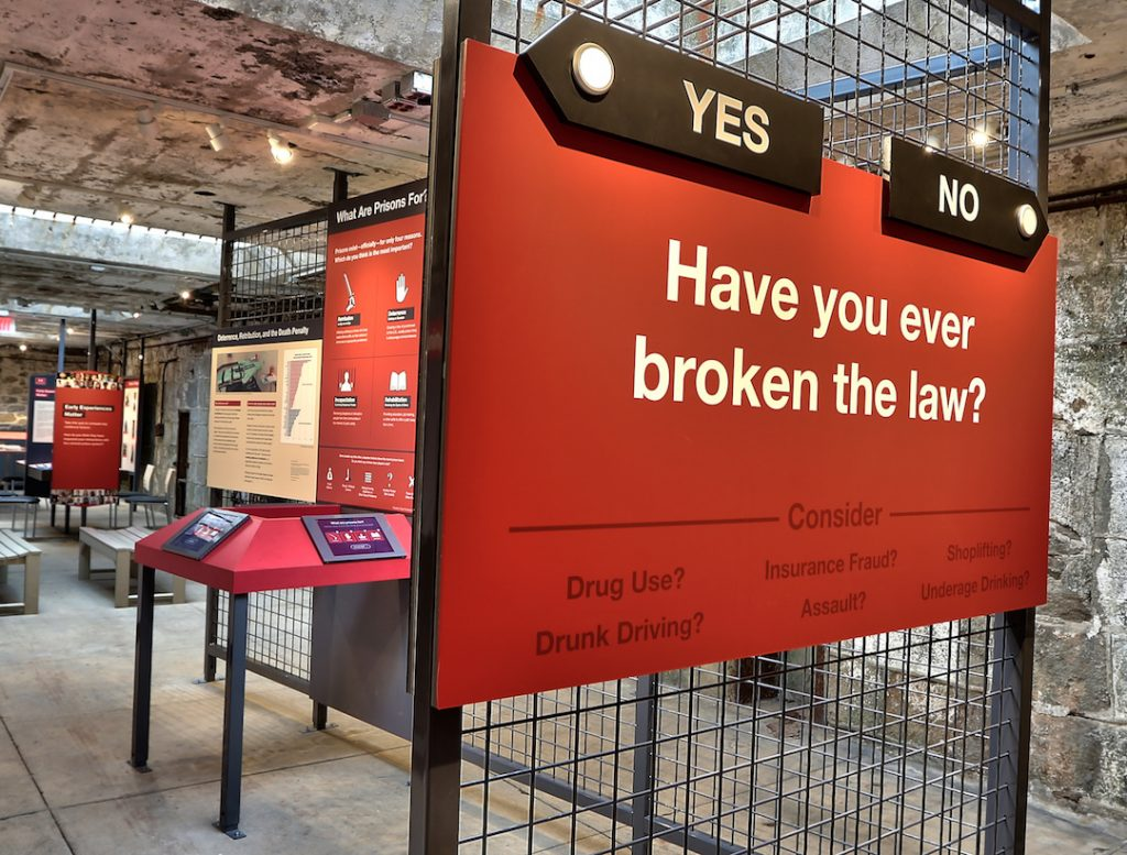 "Image of a text panel in red with yes and no arrows pointing to different routes through the exhibit with the question ""Have you ever broken the law?"""