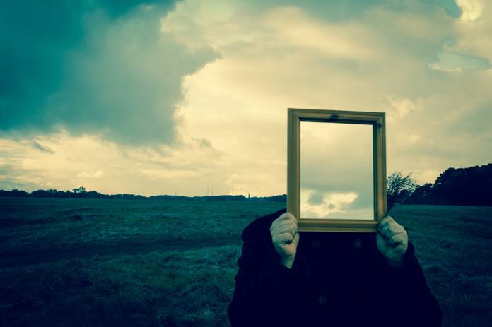 A person holding up a mirror backwards where it shows the sky instead of a face.
