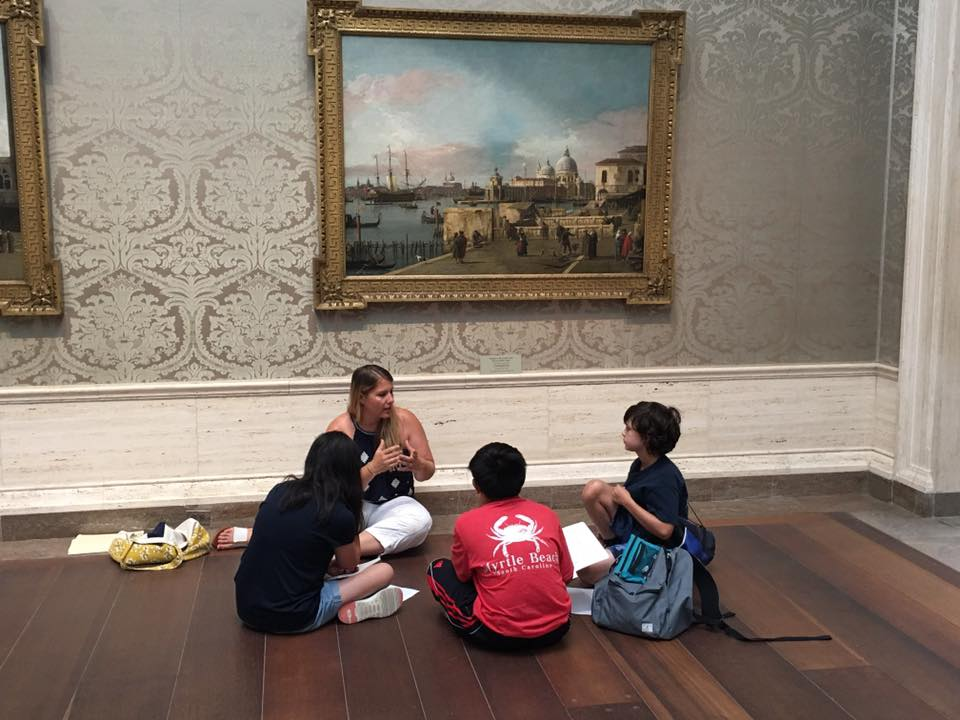 Field trip to the National Gallery with children sitting on the floor in front of a painting with a teacher sitting and interpreting