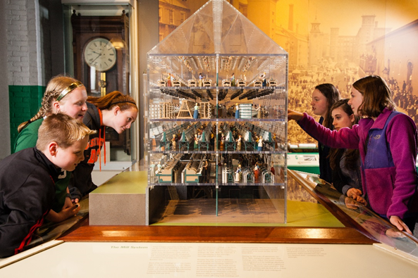 Students gather around a house shaped vitrine with miniatures inside