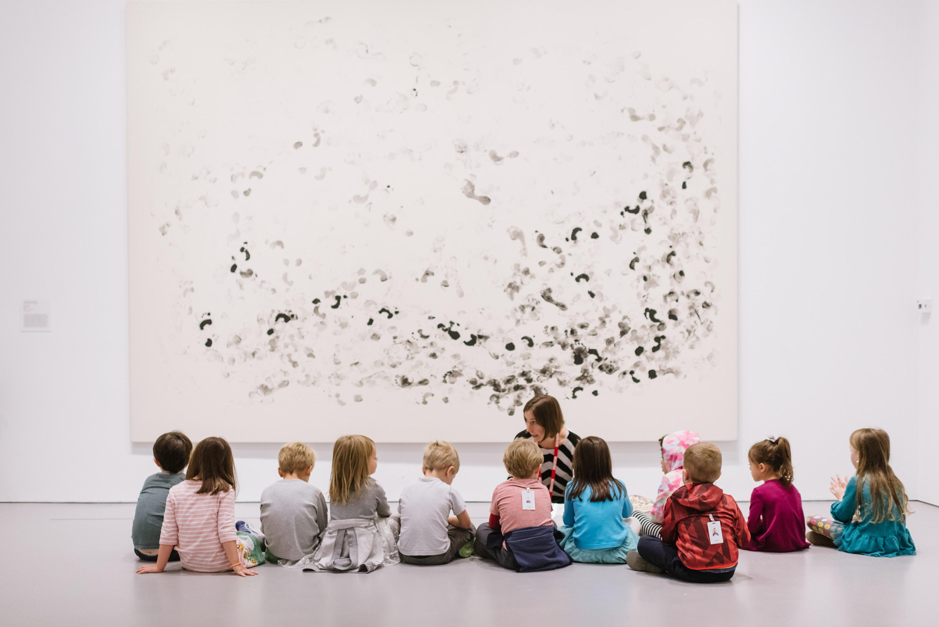 Group of small children sitting in front of an artwork in a museum gallery