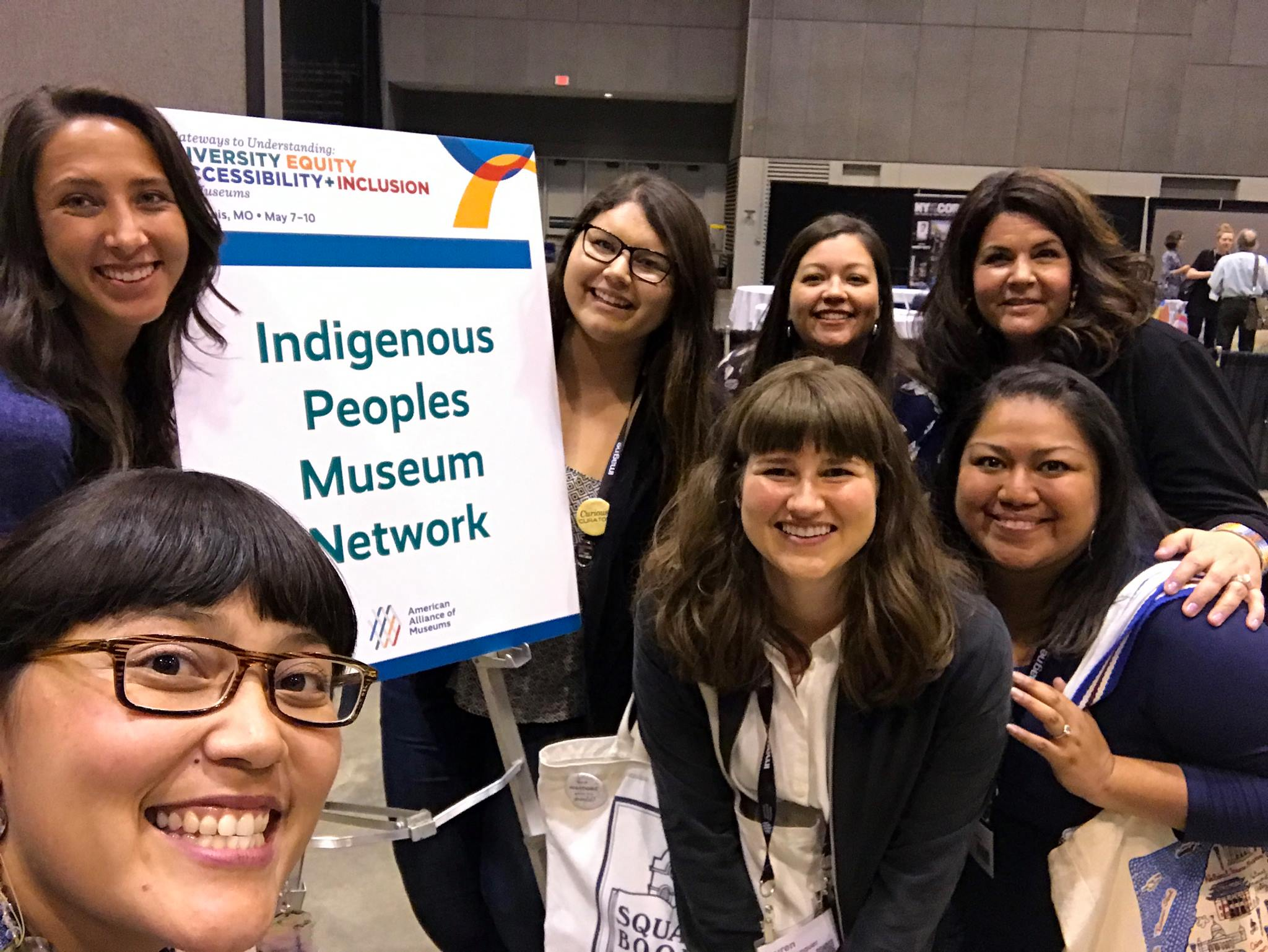An image of a group of people next to a sign for the Indigenous Peoples Museum Network professional network. They are smiling and standing together.