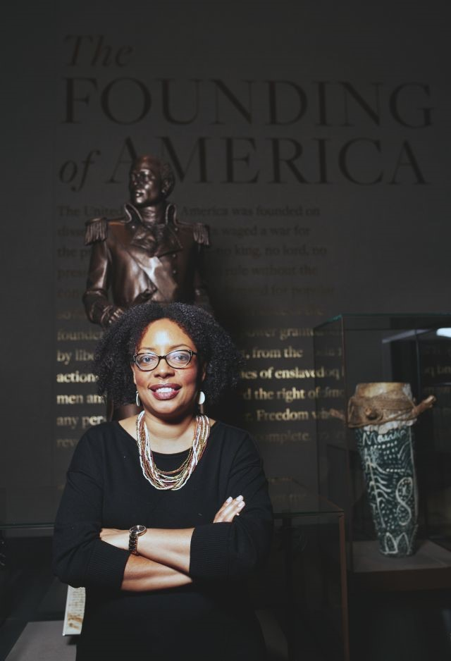 Headshot of Joanne Hyppolite standing in front of a tall sculpture on a dark wall background