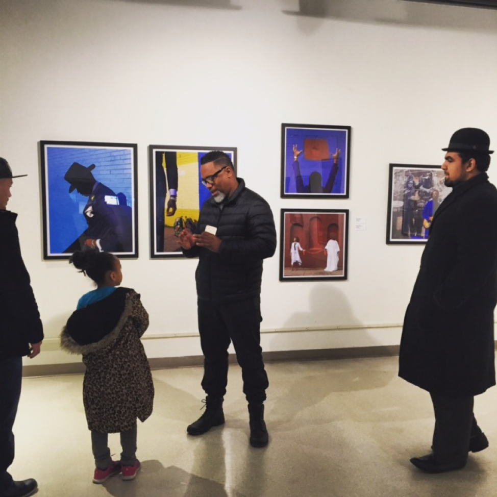 A man speaking to a young girl in an art gallery with multiple pictures hanging on a white gallery wall behind them