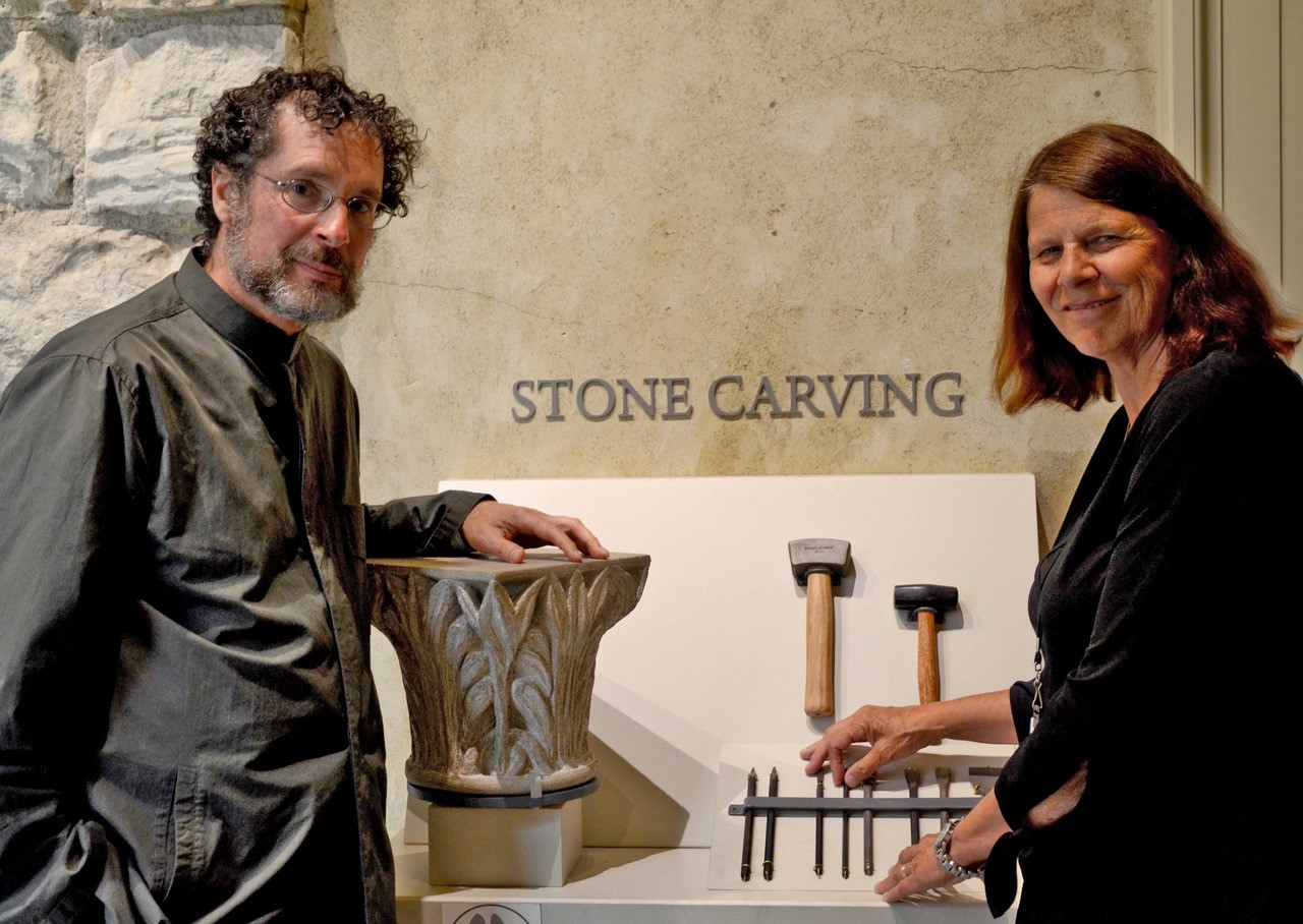 A man and a women standing together in front of a display with a column and stone carving tools