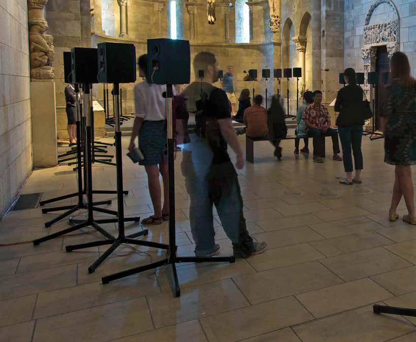 People milling around in a large highly decorative room with speakers at various intervals set up in a circle.