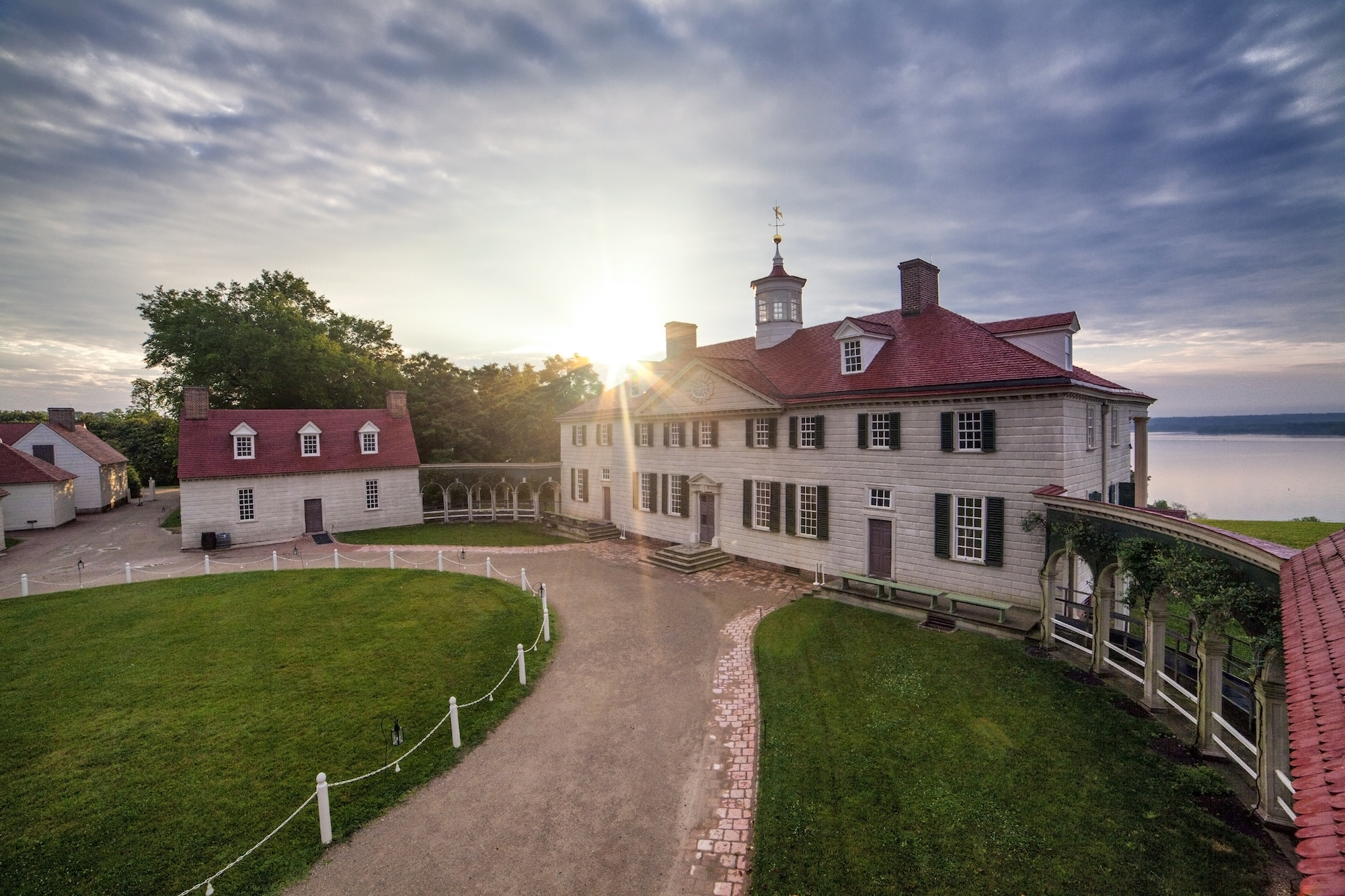 Image: Mt Vernon mansion at sunrise with the sun glinting off the roof and a green lawn stretching to the foreground