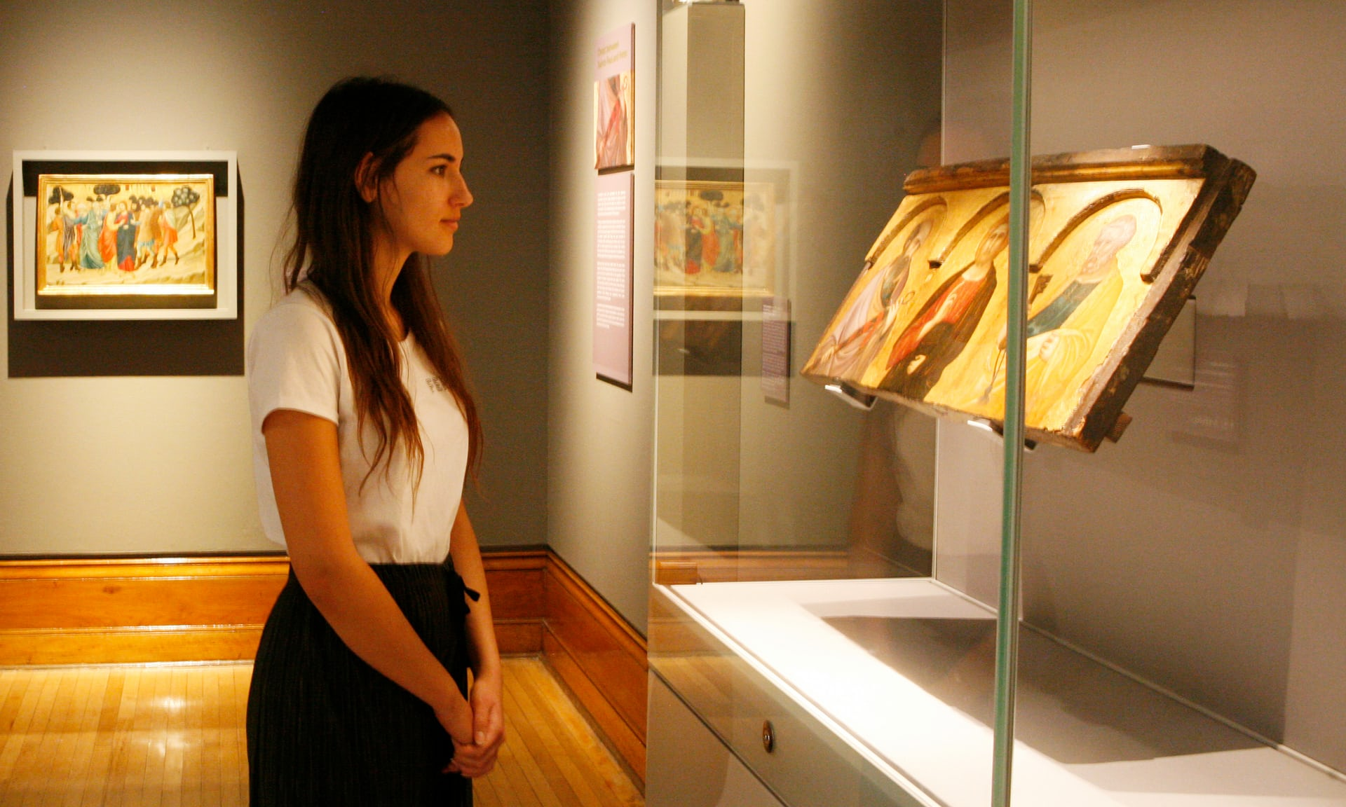 Young woman looking at a an altarpiece painting