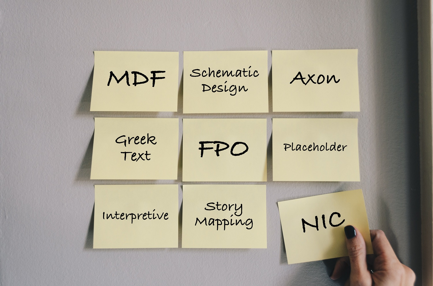 Image of 12 Post-It notes on a wall with various acronyms or design words. Top row: MDF, Schematic Design, Axon. Second row: Greek Text, FPO, Placeholder. Third row: Interpretive, Story Mapping, NIC. The final note is being held by a woman's hand wearing dark nail polish.