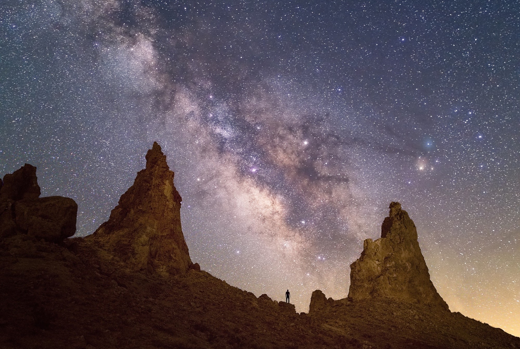 Image of the night sky with several sharp peaks in the foreground and a small person standing.
