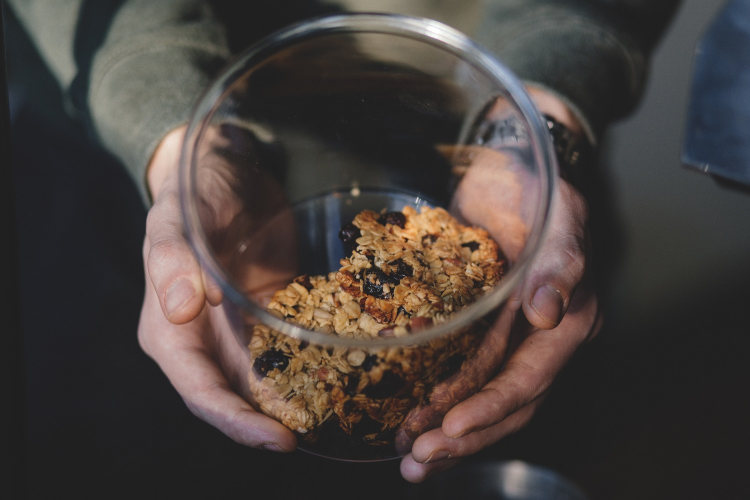 Image of a pair or hands holding a clear glass cookie jar with what look like oatmeal and raisin cookies inside. Shot taken from above looking down into the jar at an angle.