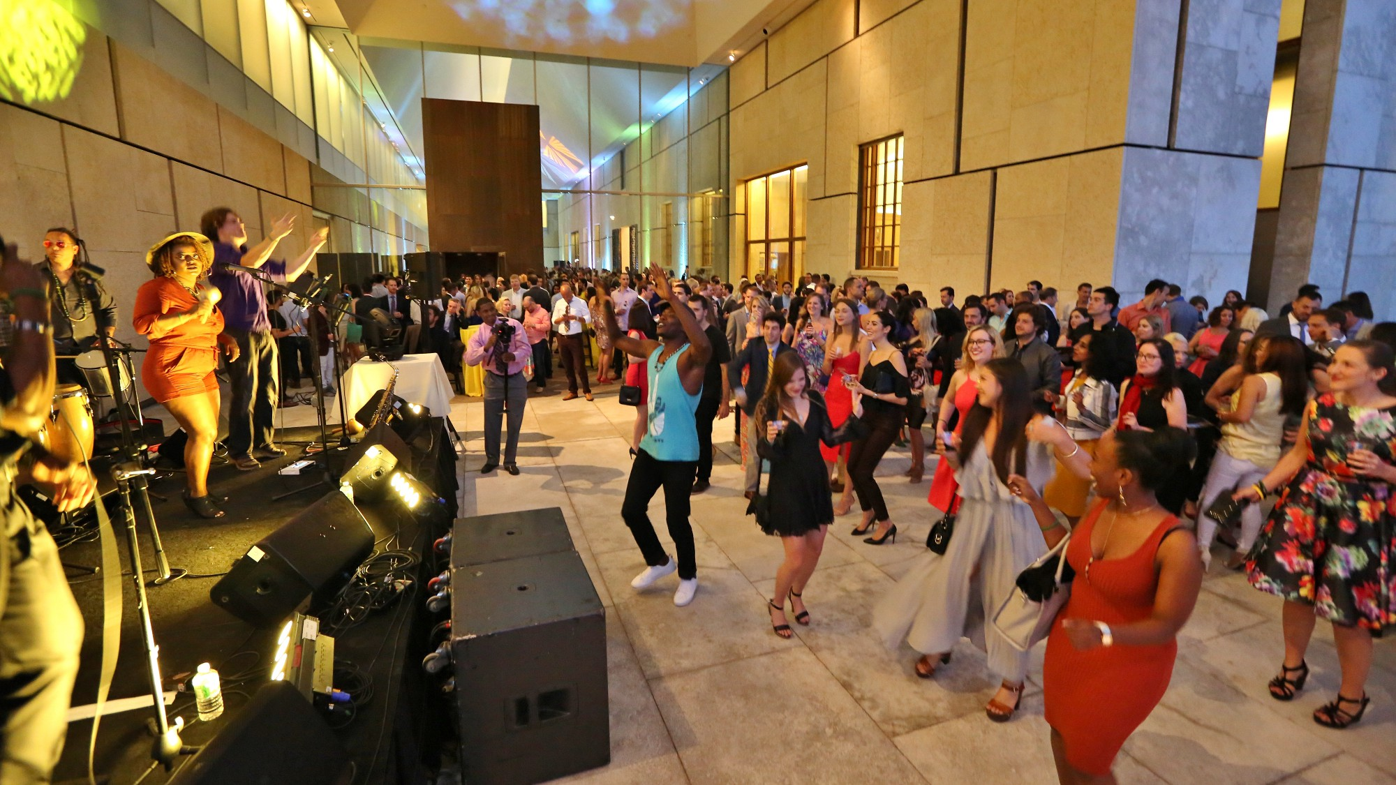 A group of young people are dancing in the atrium of the museum to music from the stage on the left of the image