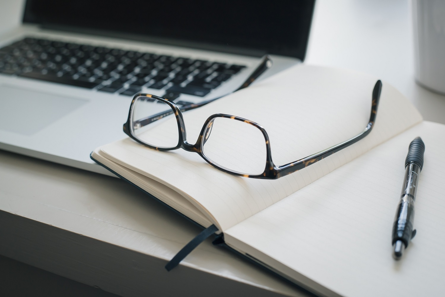 Image of a laptop blurred in the background with an open book and a pair of horn rimmed glasses sitting on the book.