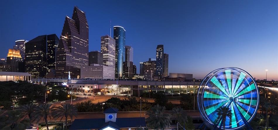 An image of the Houston skyline at sunset with skyscrapers in the background and a ferris wheel lit with blue lights in the foreground
