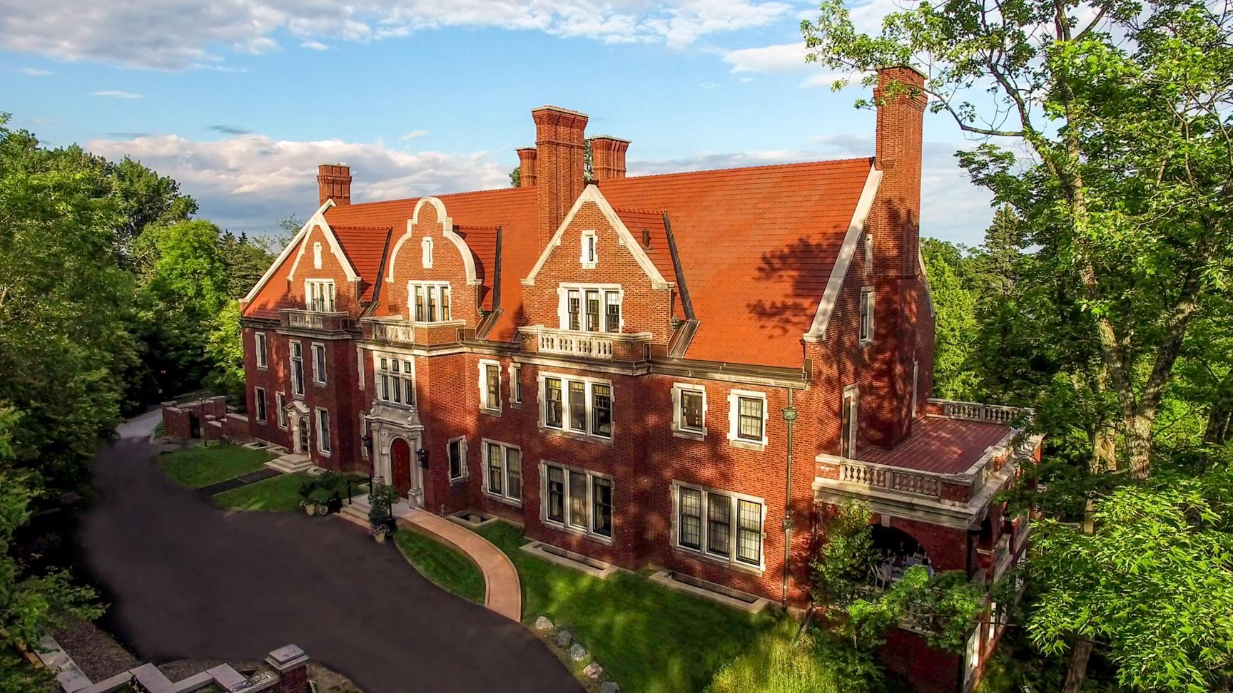 Image of the front of Glensheen house, a red brick Jacobean style mansion with a blacktop road and curved wheelchair ramp visible in front.
