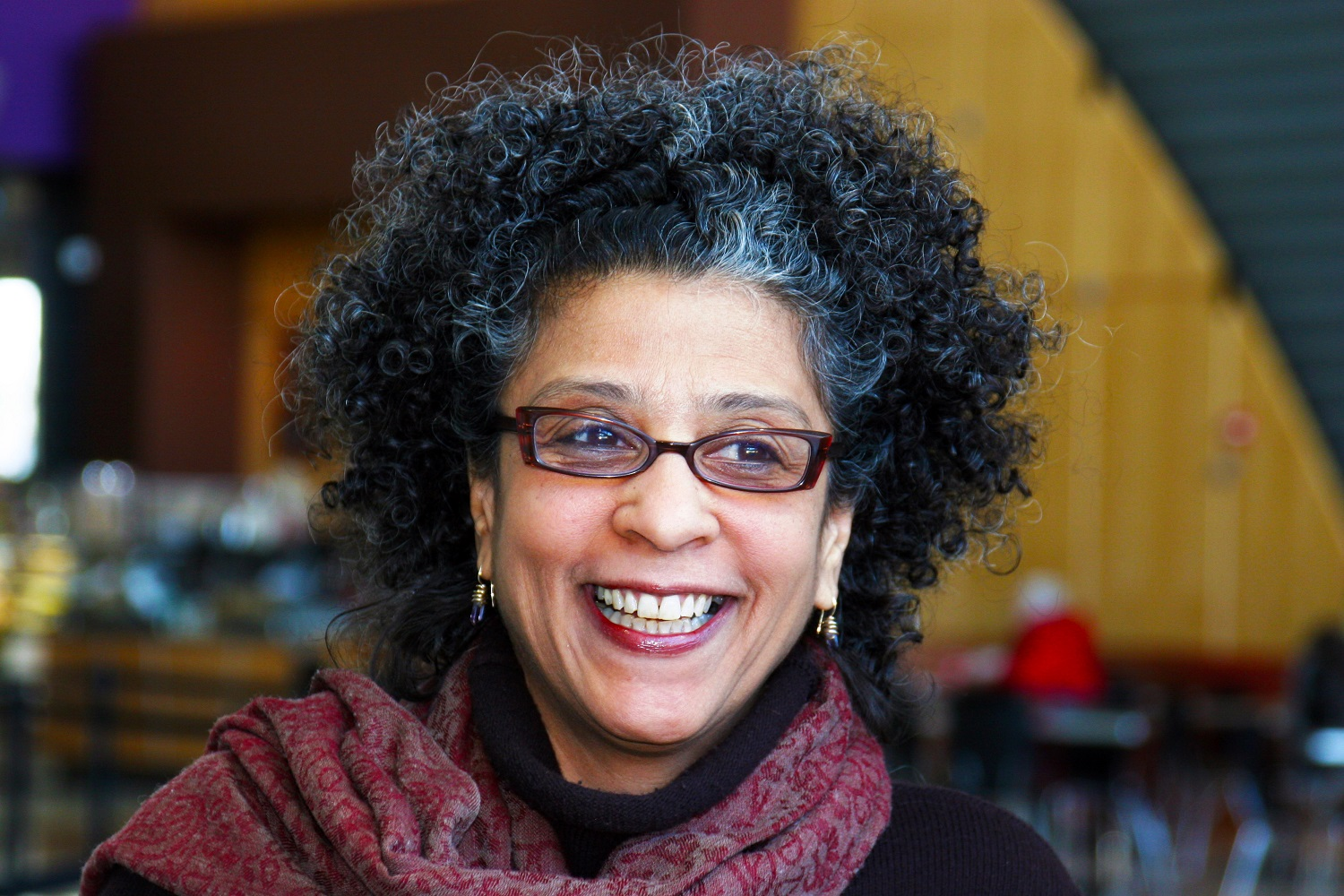 A woman smiling looking off into the distance with short curly black hair with bit of grey wearing red rimmed glasses and dangling earrings with a pink scarf around her neck.