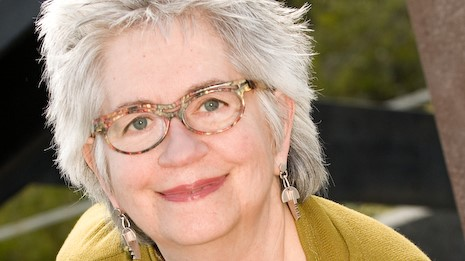 Headshot of Kathleen McLean smiling at the camera with short spikey white hair wearing multi-colored glasses and long dangling earrings with a mustard colored jacket.