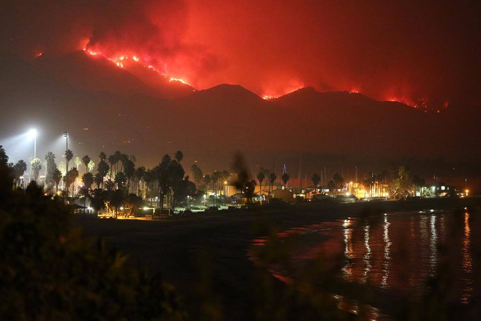 Image shows a beach area with a populated area and lights and in the background a mountain area with a red fire line all along it.