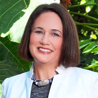 Headshot of Donna McGinnis standing in front of greenery smiling at the camera her head slightly tilted wearing a light colored jacket and chunky necklace. She has short straight brown hair.