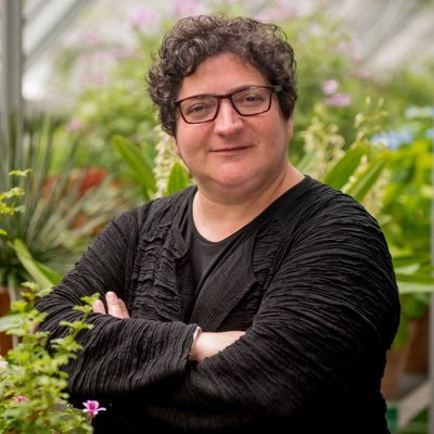 A woman stands in a greenhouse wearing a black blouse with her arms folded in front of her