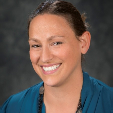 Headshot of Pam Swartz smiling at the camera in front of a generic grey backdrop.