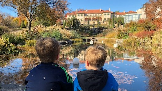 Two young boys sit on a rock and look across a pond to a large Spanish style mansion on a hill.